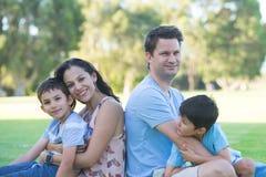 室外愉快的人种间家庭的公园 免版税库存图片