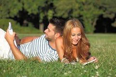 室外愉快的夫妇的阅读书 库存图片