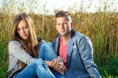 室外愉快的微笑的年轻的夫妇 在红色玫瑰色华伦泰白色的概念重点 免版税库存图片