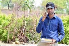 室外愉快的时髦的印地安年轻商人的阅读书 库存照片