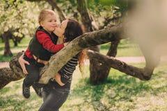 室外愉快的年轻母亲和小孩的儿子一起走和使用 免版税库存图片