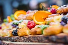 室外承办的自助餐的食物 蛋糕五颜六色的新鲜水果莓果桔子葡萄和草本装饰 免版税库存图片