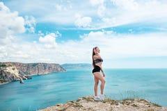 室外摆在晴朗的天气的海的年轻性感的肉欲的被晒黑的体育妇女夏天海滩热带画象和 免版税图库摄影