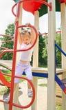 室外操场设备的愉快的小女孩 图库摄影
