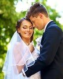 室外新郎亲吻的新娘的夏天 免版税库存照片