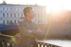 室外时尚的衣服的英俊的人 太阳阴霾 图库摄影
