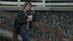 室外有吸引力的白肤金发的少妇饮用的咖啡 影视素材