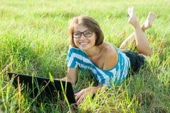 室外有膝上型计算机的画象微笑的中年妇女自由职业者博客作者旅客在自然 免版税图库摄影
