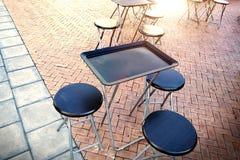 室外桌和两把椅子在墙壁附近在咖啡店 免版税库存照片