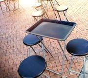 室外桌和两把椅子在墙壁附近在咖啡店 免版税库存图片
