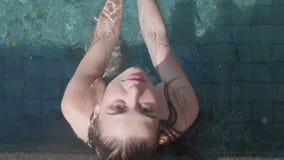 室外水池的年轻俏丽的妇女 免版税库存图片