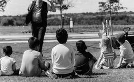 室外游戏草草甸的被过滤的图象特写镜头背面图多文化孩子  免版税库存照片