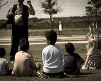室外游戏草草甸的被过滤的图象特写镜头背面图多文化孩子  免版税库存图片