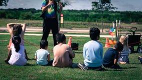 室外游戏草草甸的被过滤的图象特写镜头背面图多文化孩子  库存图片
