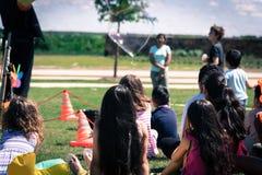 室外游戏草草甸的被过滤的图象特写镜头背面图多文化孩子  库存照片
