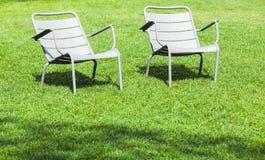 室外灰色金属椅子在新鲜的草站立 免版税库存照片