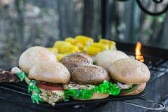室外烤的汉堡 用乳酪,葱,沙拉,蕃茄 免版税库存照片