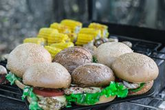 室外烤的汉堡 用乳酪,葱,沙拉,蕃茄 免版税库存图片