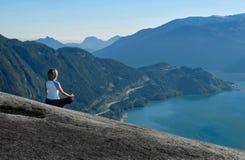 室外瑜伽撤退 莲花姿势的妇女思考在山上面的有美丽的景色 库存图片