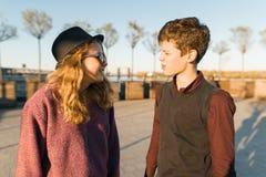 室外画象两三年轻看彼此,日落光的,金黄小时微笑的少年的男孩和女孩 库存照片