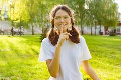 室外画象een展示平静地签字的女孩,秘密,在她的嘴唇附近的举行手指 背景日落的城市公园 库存图片