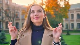 室外白种人的女孩,站立隔绝与镇静愉快的神色,并且祝愿与她的手指的运气横渡了,绿色 股票视频