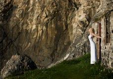 室外白色长的礼服的美丽的白肤金发的妇女,在一个被破坏的大厦旁边的门享受阳光在爱尔兰 免版税库存图片