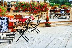 室外的咖啡馆 椅子和桌在大阳台与花 免版税库存照片