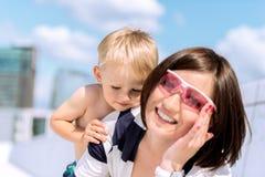 室外的母亲和的儿子的可爱的画象获得乐趣 图库摄影