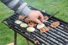 室外的烤肉 在格栅的人的手被烘烤的丸子 免版税库存照片
