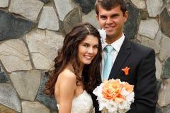 室外的爱的愉快的美丽的年轻新娘拥抱新郎 图库摄影