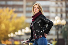 年轻室外的皮夹克的时尚白肤金发的妇女 库存照片