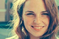 室外的秀丽 微笑的年轻和愉快的妇女画象有雀斑的 库存图片