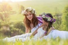 2室外的美丽的新娘,坐田园诗的草- 免版税图库摄影