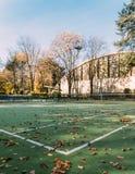 室外空的网球场的角落秋天叶子的 库存图片
