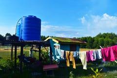 室外简单蓝色塑料储水池和小屋和衣裳烘干 免版税库存图片