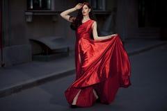 室外红色的礼服的新秀丽妇女 免版税库存照片