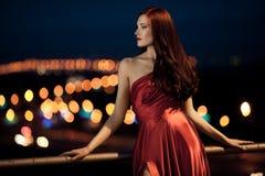 室外红色的礼服的新秀丽妇女 免版税库存图片