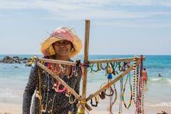 室外纪念品店的女性贸易商在海滩 免版税图库摄影