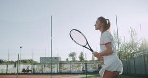 室外网球场,一专业球员女性使用与她的伙伴专家被装备,好晴天 4K 股票录像