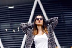 室外羊毛衫、的衬衣和的太阳镜的美丽的女孩 免版税图库摄影
