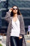 室外羊毛衫、的衬衣和的太阳镜的美丽的女孩 免版税库存图片