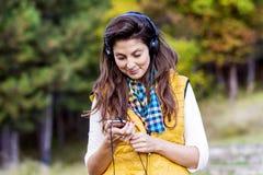 室外美好的少妇听的音乐画象  享受音乐 库存照片