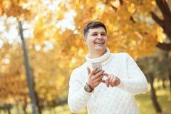 室外美好的橙色的秋天!停留在公园和使用他的有微笑的毛线衣的英俊的年轻人智能手机在他的面孔 库存照片