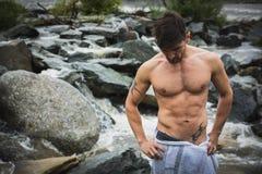 室外英俊的肌肉年轻的人佩带仅毛巾 免版税库存照片