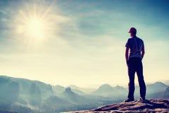 室外衣裳的高人在岩石峰顶单独站立  免版税图库摄影