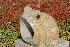 室外被雕刻的青蛙形状石头垃圾箱 图库摄影