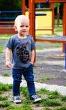 室外逗人喜爱的微笑的男孩 免版税库存图片