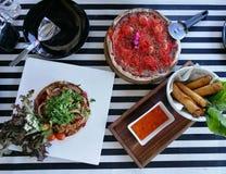 室外野餐党用薄饼、烤牛排和春卷在黑白小条桌布在雀鳝 免版税库存图片