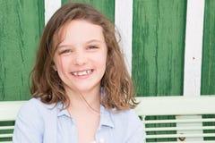 室外长凳的绿色的微笑的秀丽女孩 库存图片